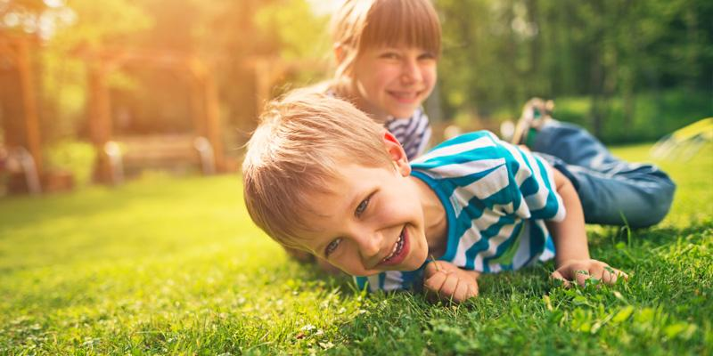 Two young kids playing in a fire ant-free backyard