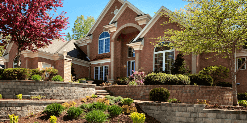 beautiful brick home surrounded by trees with red and green foliage