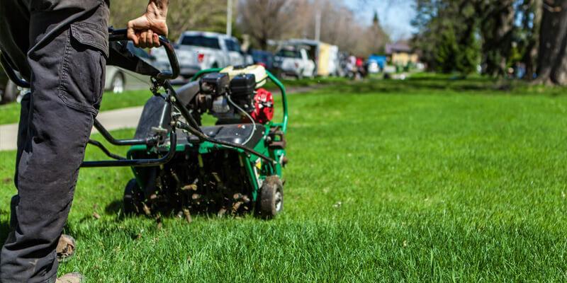 A lawn technician pushing an aerator machine